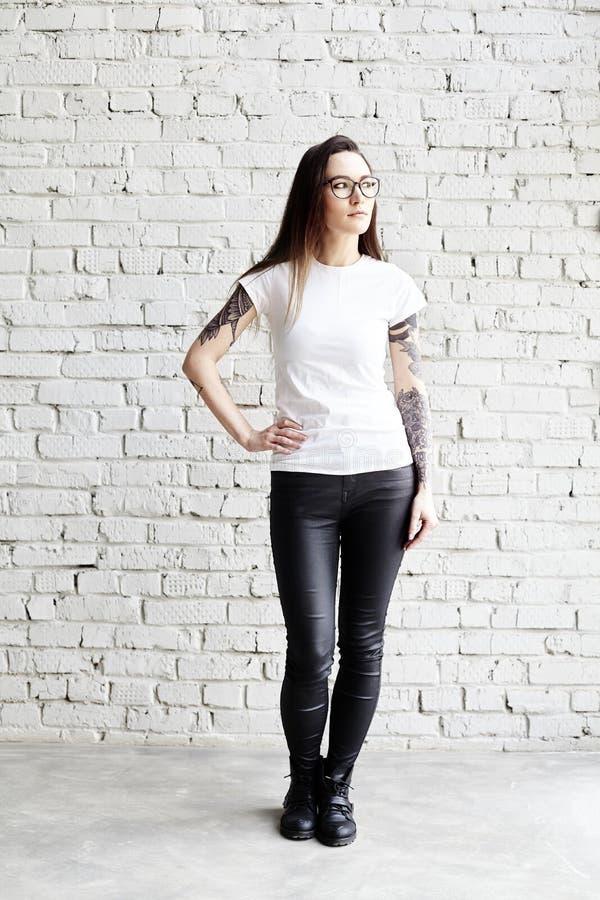 Barnet tatuerade kvinnan som bär den tomma t-skjortan som framme står av tegelstenväggen i vind royaltyfria foton