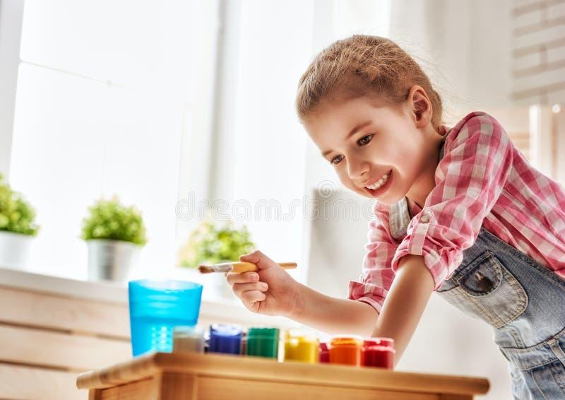 barnet tecknar målarfärger royaltyfri fotografi
