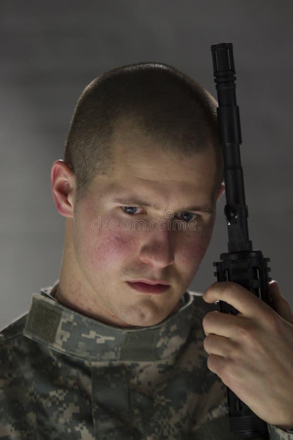 Barnet tjäna som soldat att se ledset & benägenhet på anfallgeväret arkivbilder