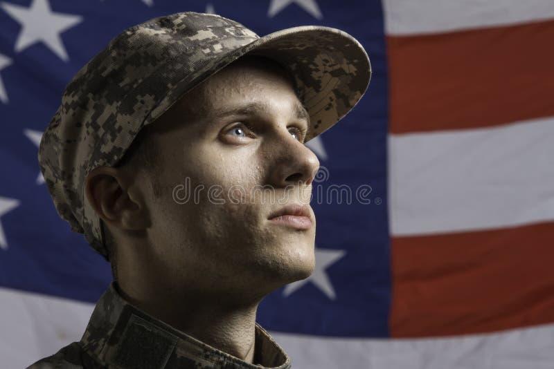 Barnet tjäna som soldat poserat framme av amerikanska flaggan, horisontal arkivbild