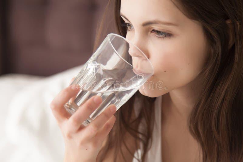 Barnet torkade kvinnan som känner sig törstig och att dricka mineralvatten f arkivbilder