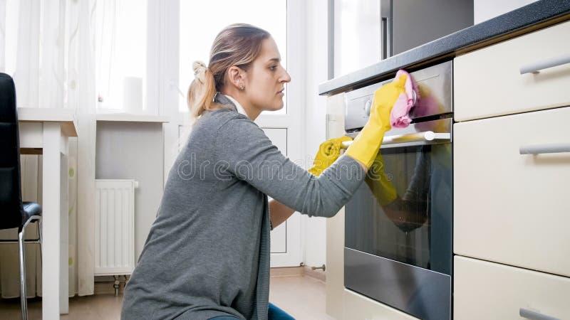 Barnet tröttade hemmafrun i latexhandskar som gör ren ugnen på kök royaltyfri fotografi