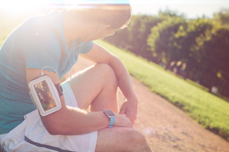 Barnet tröttade idrottsman nen med armbindeln som vilar i parkera royaltyfri fotografi