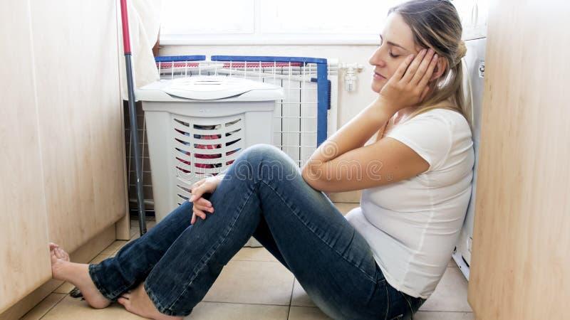 Barnet tröttade kvinnan som sover på golv på tvättstuga, når de har gjort hushållsarbete arkivfoton