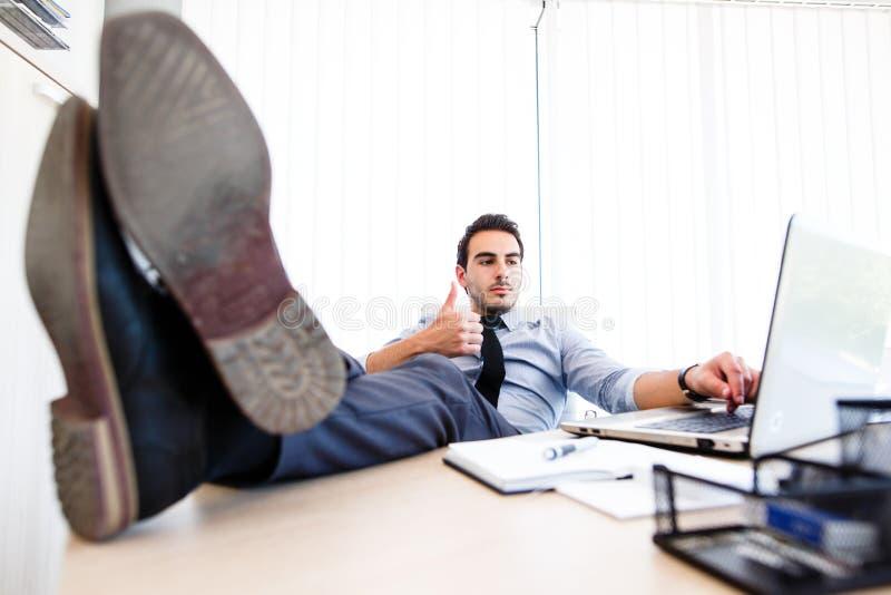 Barnet tröttade upp affärsmannen på arbetsplatsen - tumme som motivational gest royaltyfri fotografi