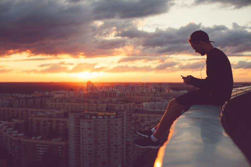 Barnet trotsar mansammanträde ovanför staden med smartphonen på solnedgången arkivbild