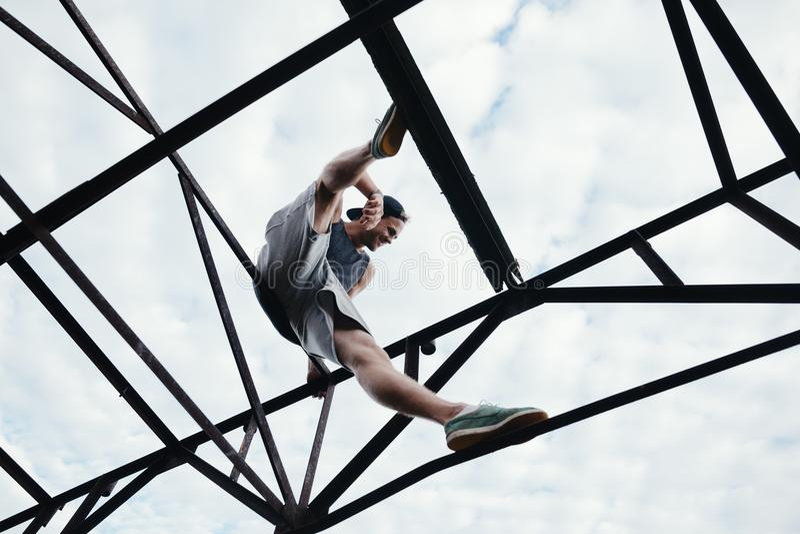 Barnet trotsar mansammanträde på överkanten av konstruktion för hög metall royaltyfria foton