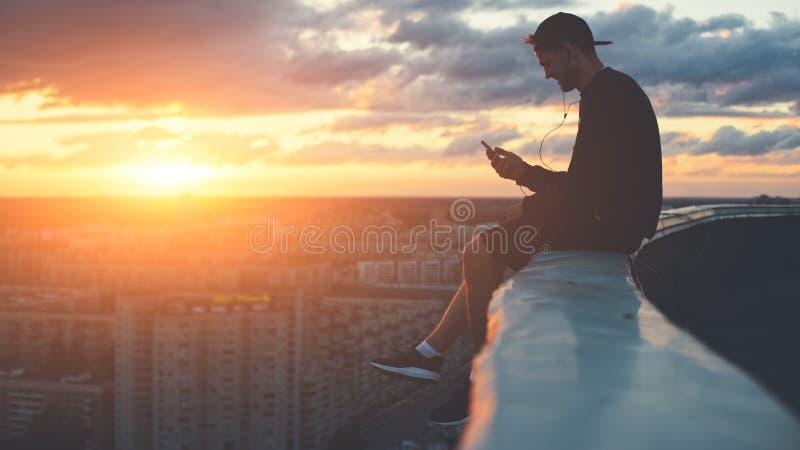 Barnet trotsar mansammanträde på kanten av taket med smartphonen på solnedgången royaltyfri fotografi