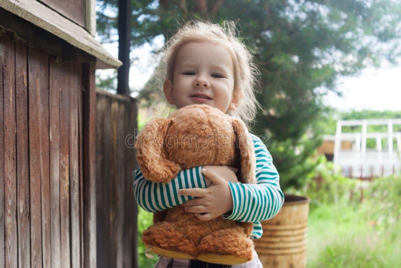 Barnet trycker på det lilla djuret till hans bröstkorg och leenden på en solig dag i aftonen nära landshuset fotografering för bildbyråer