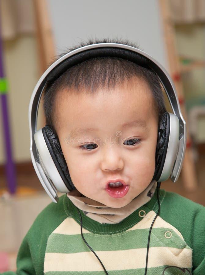 barnet tycker om musik arkivfoton