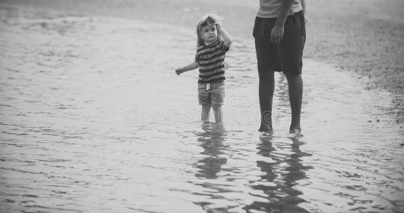Barnet under vuxen övervakning går i vatten på havsstranden royaltyfri foto