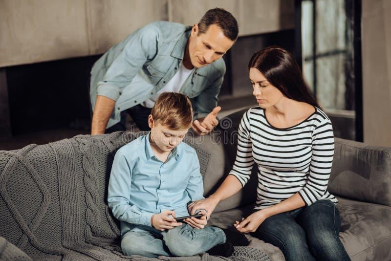 Barnet uppfostrar att övertyga deras son för att stoppa att spela på telefonen arkivbild