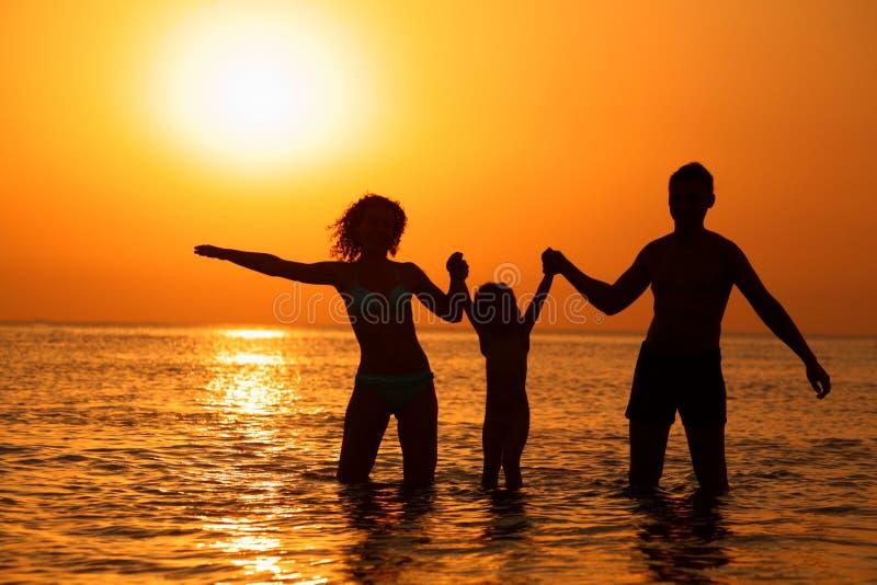 barnet uppfostrar havssolnedgång arkivfoto