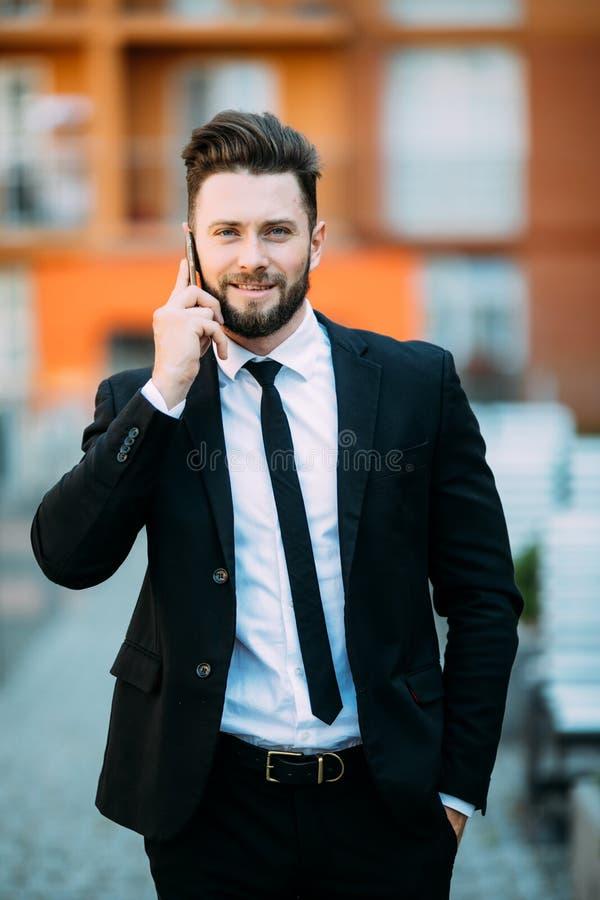 Barnet uppsökte den stiliga affärsmannen som utomhus talar på hans mobiltelefon i stadsgata royaltyfria foton