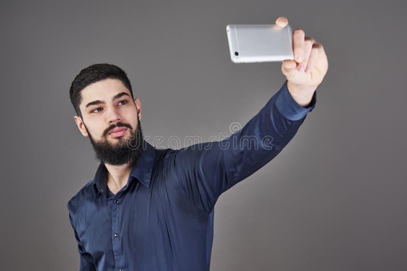 Barnet uppsökte fotoet för selfie för hipsteraffärsmannen det talande med den smarta telefonen som ler och ser telefonen mot grå  fotografering för bildbyråer