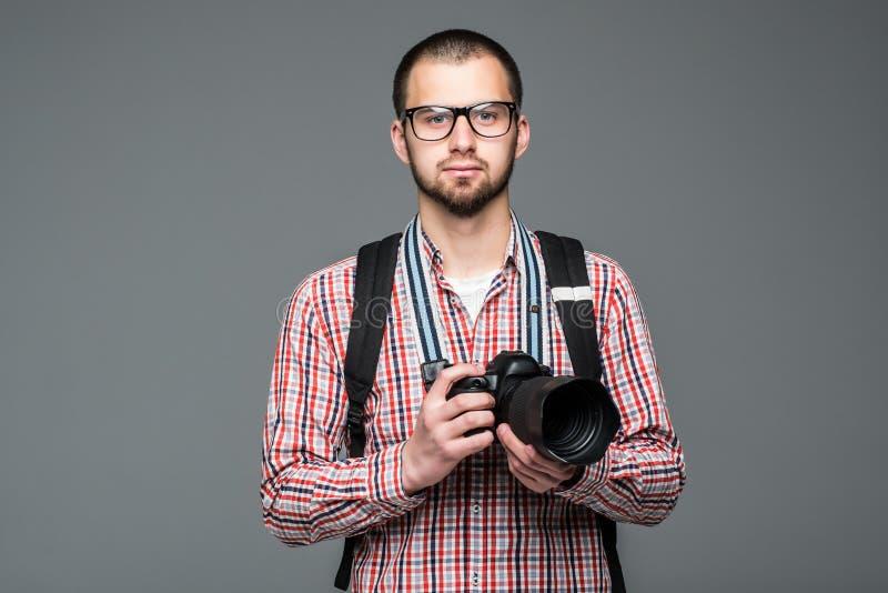 Barnet uppsökte handelsresandemannen med fotokameran på grå bakgrund royaltyfri fotografi
