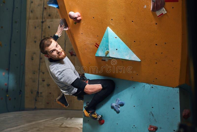 Barnet utmanade fysiskt bouldereren som hänger på den färgglade klättraväggen royaltyfri bild