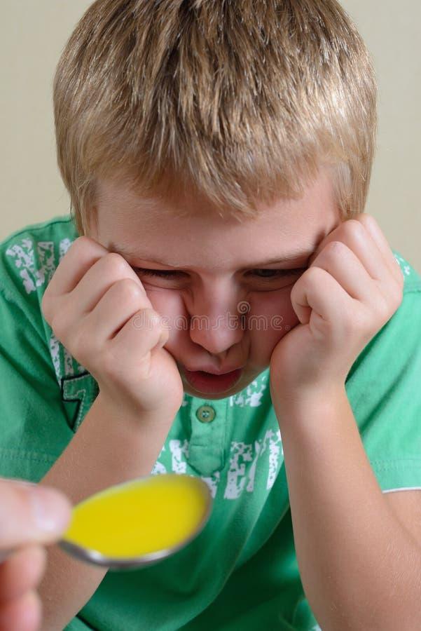 Barnet vägrar för att ta medicinen royaltyfri bild