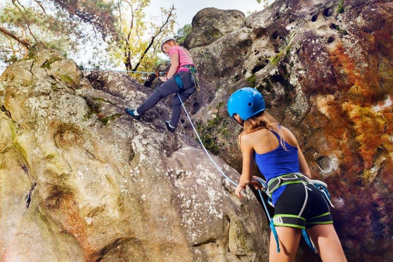 Barnet vaggar klättraren som når toppmötet av berget arkivfoto
