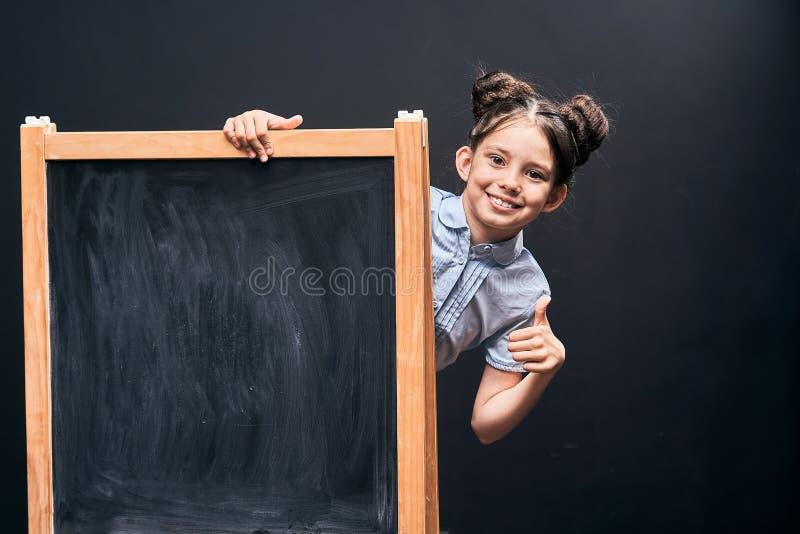 Barnet visar ett tecken av godkännande som står på skolförvaltningen positiv skolflicka som ut bakifrån kikar en svart skolförval royaltyfria foton
