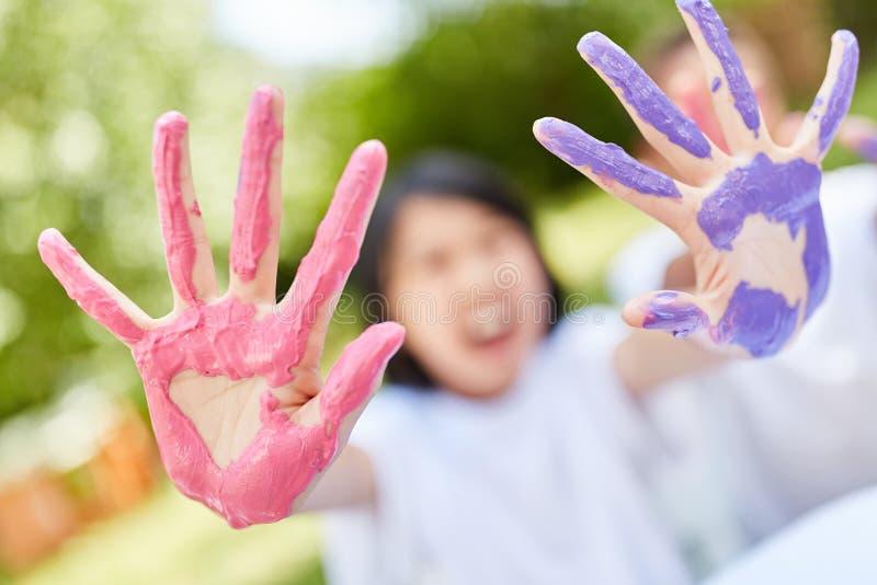 Barnet visar h?nder i purpurf?rgade och rosa f?rger arkivfoto