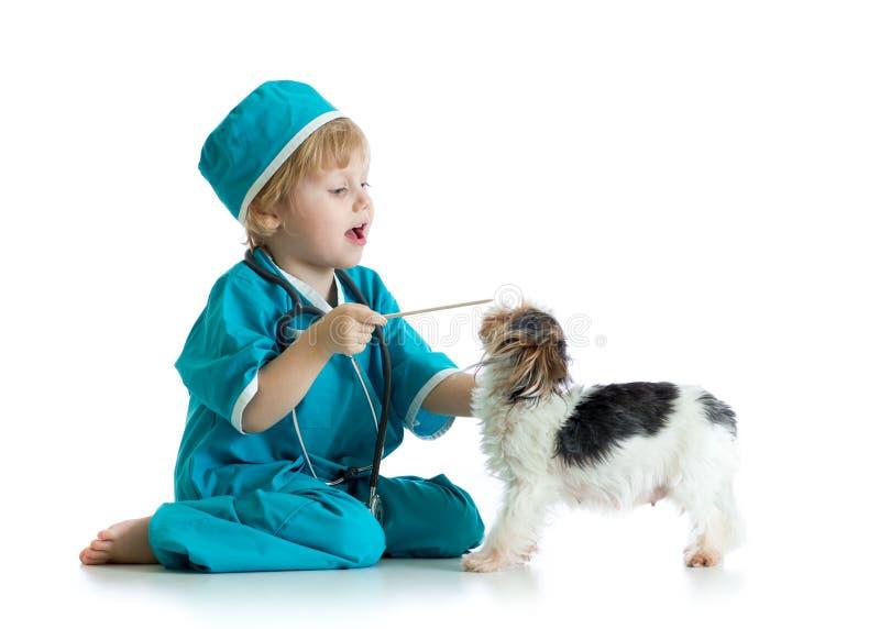 Barnet weared doktorn beklär att spela veterinären med hunden royaltyfri foto