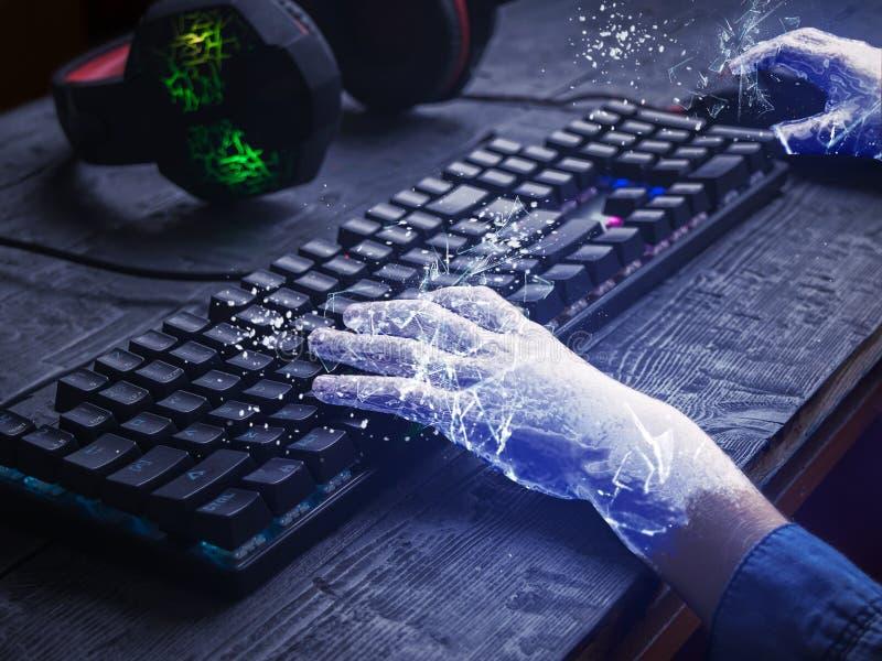 Barnets händer täckte med is på tangentbordet och spelahörlurar på trätabellen Begreppet av beroende på datoren arkivfoto