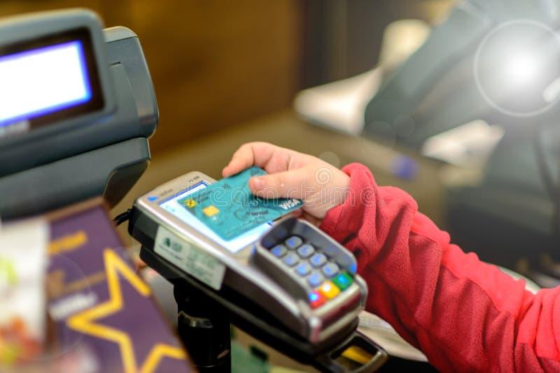 Barnets hand rymmer kreditkorten av den Raiffeisen banken ovanför betalningterminalen för att göra en betalning arkivbilder