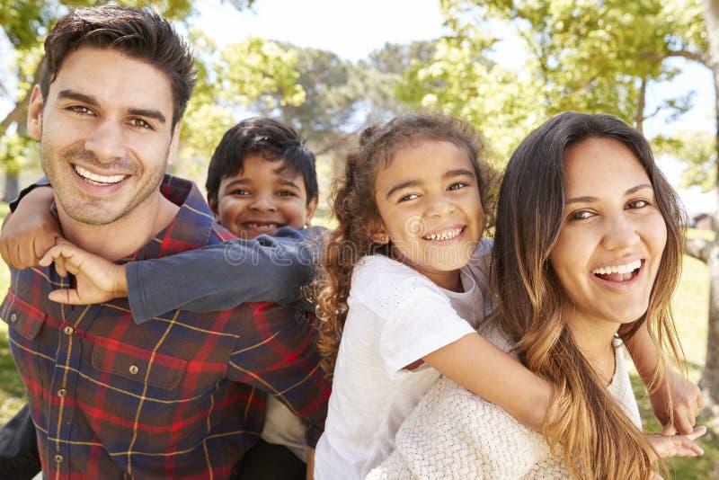 Barnföräldrar som utomhus piggybacking deras två ungar arkivbilder