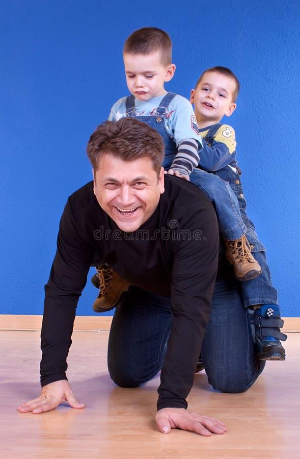 Barnfader som ger sons en ritt arkivbilder