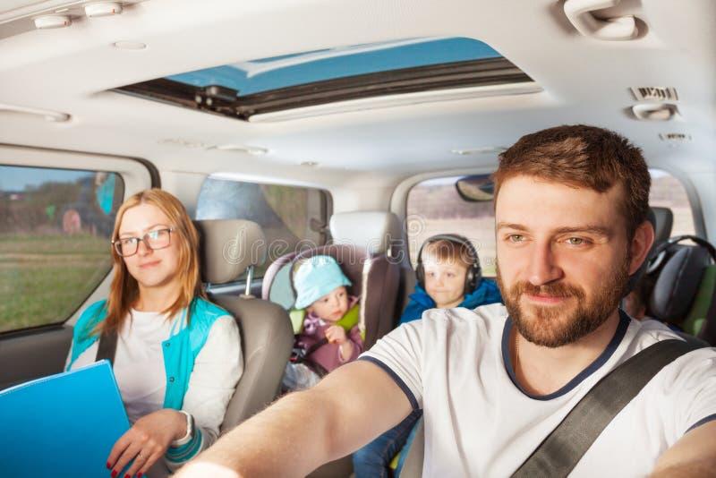 Barnfader som kör hans familjebil royaltyfri fotografi