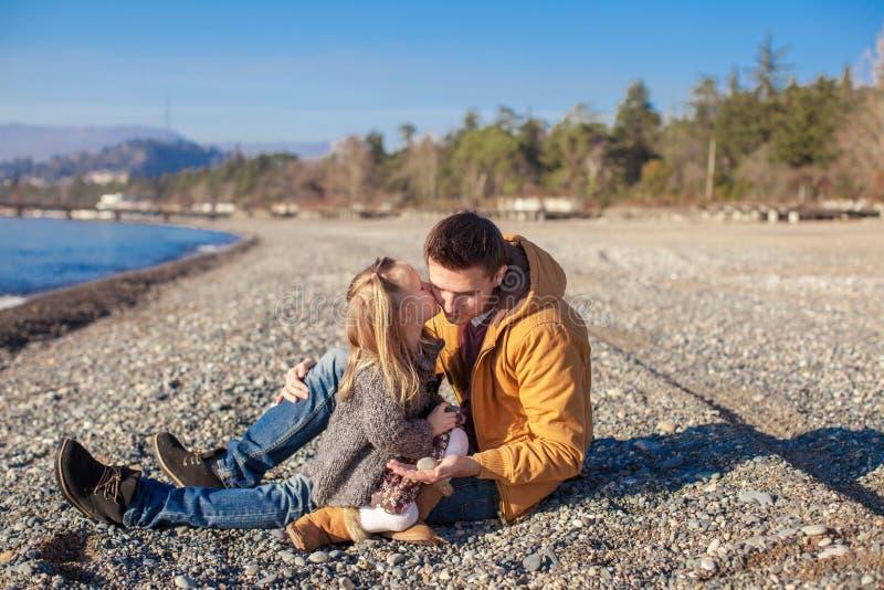 Barnfader som rymmer den lilla dottern som kysser honom royaltyfria foton