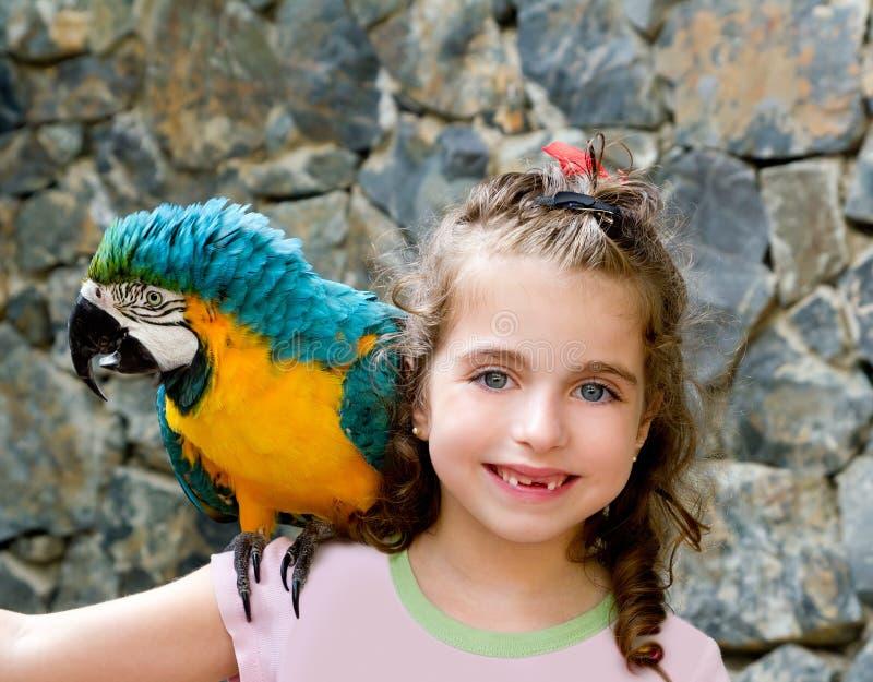 Barnflicka för blåa ögon med den gula papegojan arkivfoto