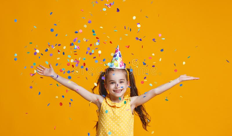 Barnflicka för lycklig födelsedag med konfettier på gul bakgrund royaltyfria bilder