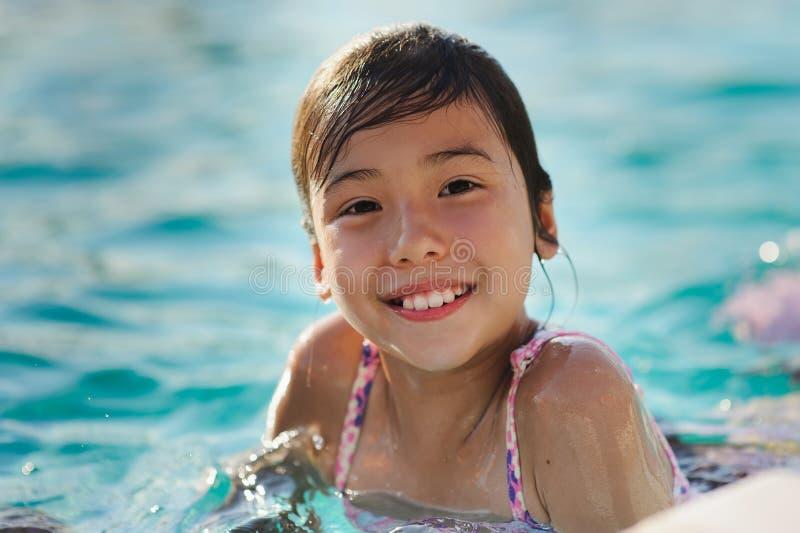 Barnflicka i blå simbassäng arkivfoto