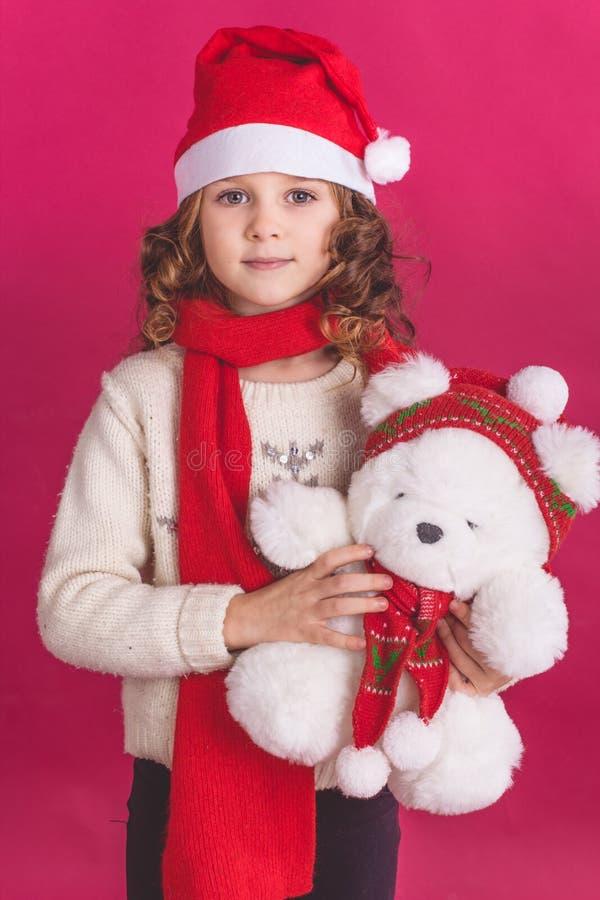 Barnflicka i den santa hatten på röd bakgrund royaltyfri fotografi