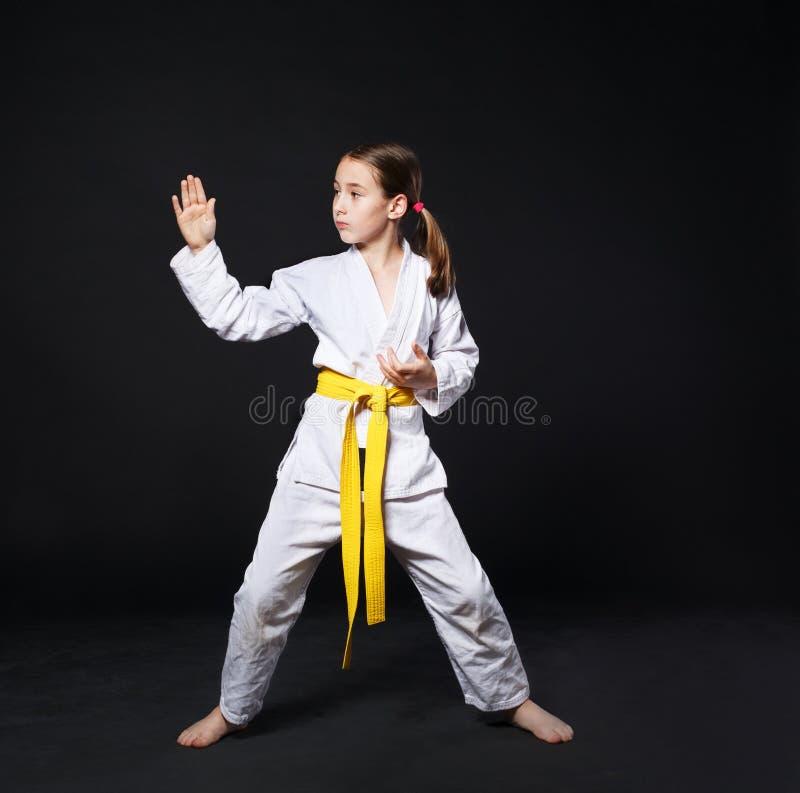 Barnflicka i karatedräkt med gul bälteshowslagställning fotografering för bildbyråer