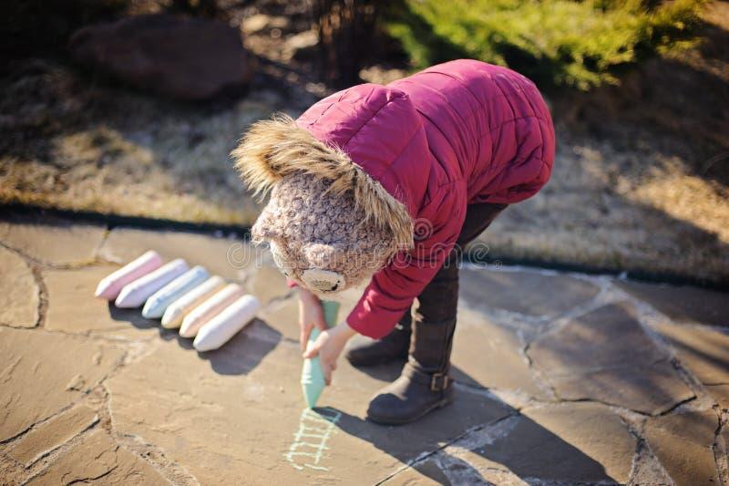 Barnflicka i rosa färgomslagsteckning med chalks i vårträdgård royaltyfri fotografi