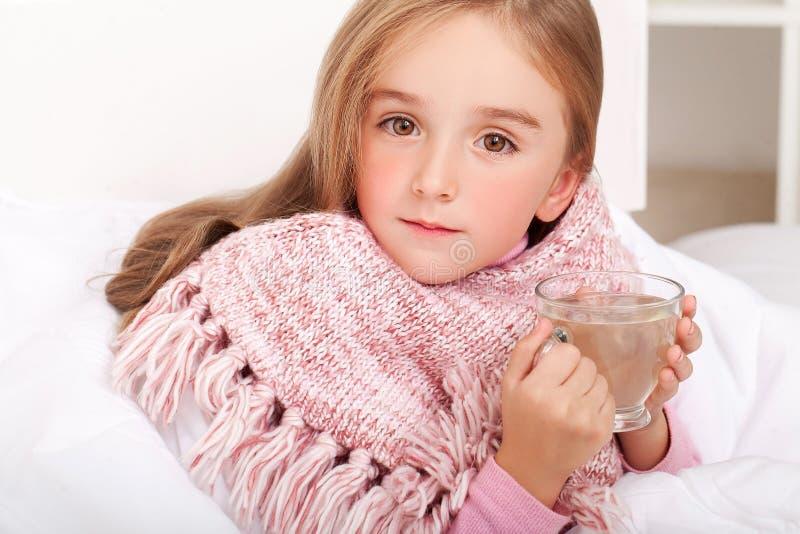 Barnflicka med en kopp av varmt te i säng royaltyfri fotografi