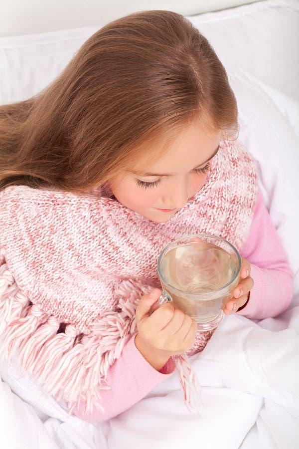 Barnflicka med en kopp av varmt te i säng fotografering för bildbyråer
