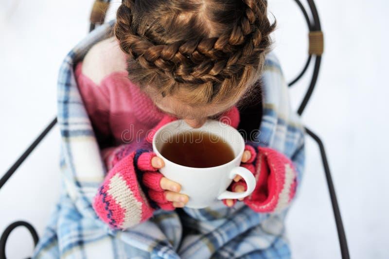 Barnflicka med en kopp av varmt te utomhus arkivbilder