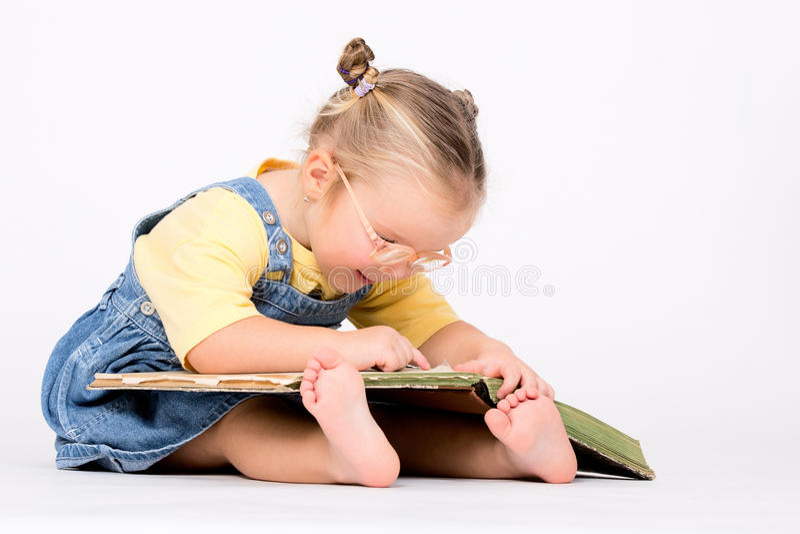 Barnflicka med exponeringsglasläseboken på vit arkivfoton