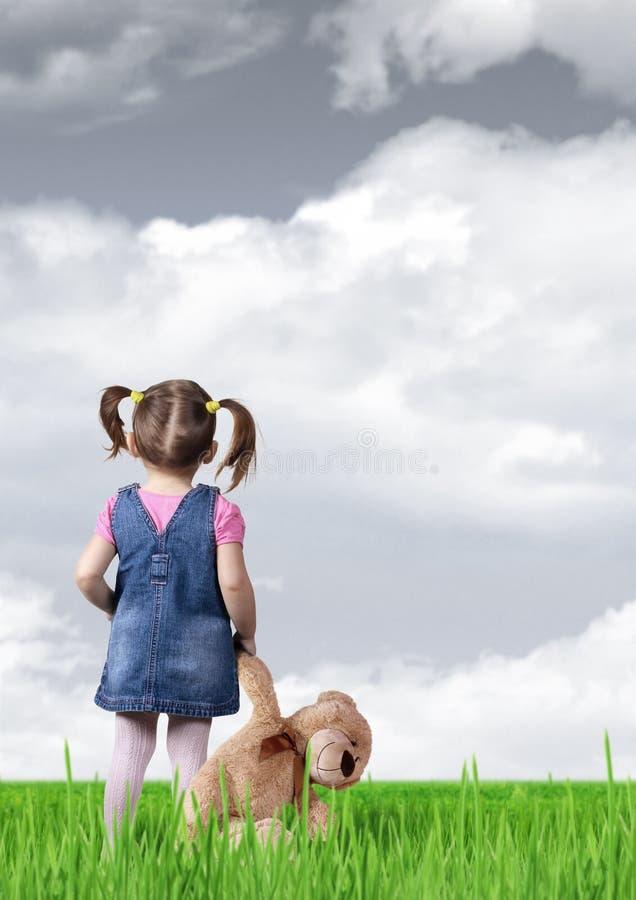 Barnflicka med leksakbjörnen som ser in i avståndet, baksidasikt arkivfoton
