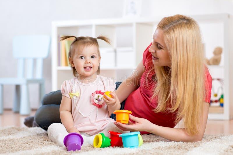 Barnflicka och moder som spelar samman med leksaker arkivfoto