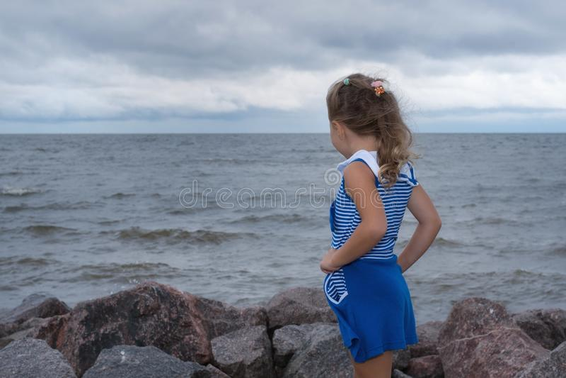 Barnflicka på havet för stormen, stark vind royaltyfria foton