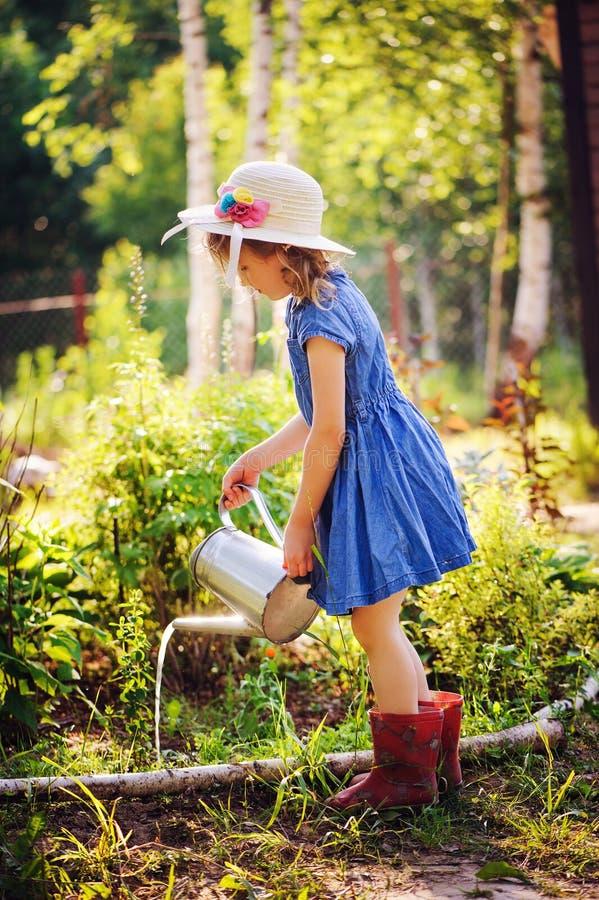 Barnflicka som bevattnar blommor i sommarträdgården, liten hjälpreda royaltyfri foto