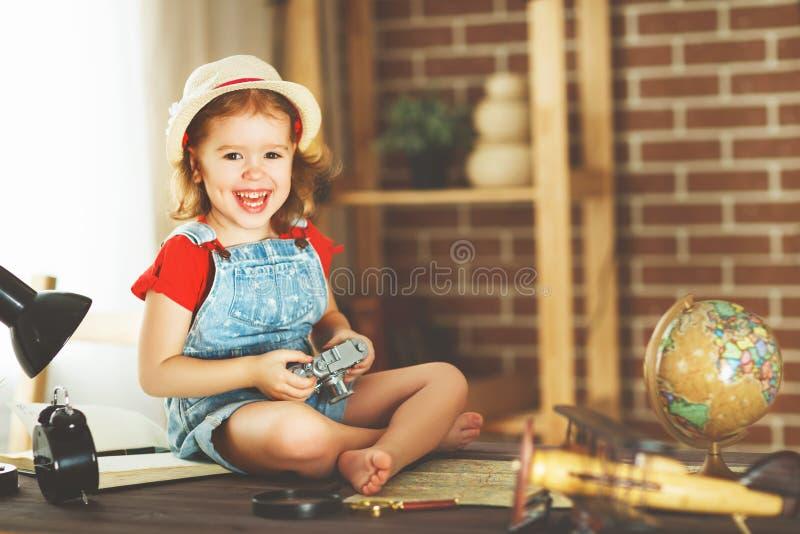 Barnflicka som förbereder sig att resa med en kort- och fotokamera royaltyfri fotografi
