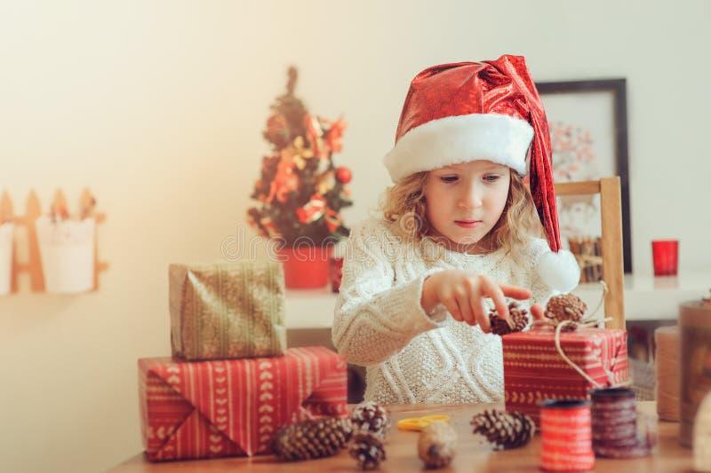 Barnflicka som hemma förbereder gåvor för jul, hemtrevlig ferieinre arkivbild