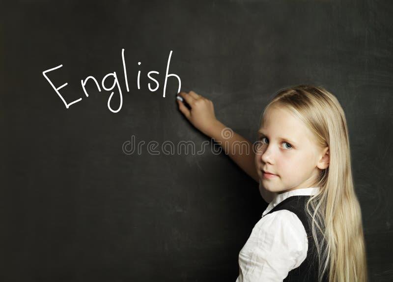 Barnflicka som lär engelska på skolaklassrumsvart tavla royaltyfria bilder