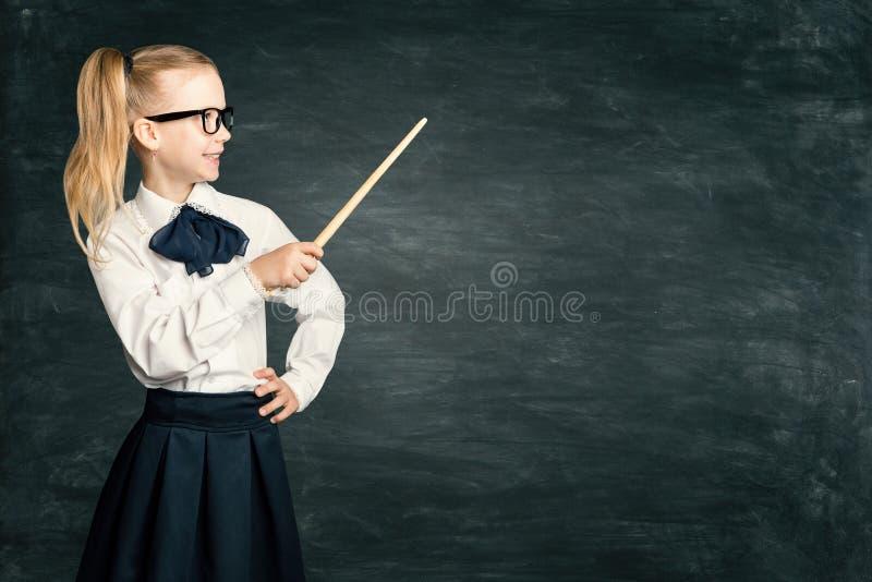 Barnflicka som pekar skolasvart tavla, elevunge i Retro klänning med pekaren över kritabräde royaltyfri foto